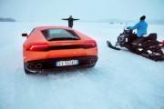 Un Lamborghini Huracan reta a una moto de nieve